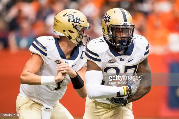 Running back Qadree Ollison of the Pittsburgh Panthers takes the hand off from quarterback Max Browne during the first half against the Syracuse...