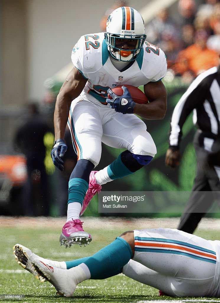 Running back <a gi-track='captionPersonalityLinkClicked' href=/galleries/search?phrase=Reggie+Bush&family=editorial&specificpeople=183392 ng-click='$event.stopPropagation()'>Reggie Bush</a> #22 of the Miami Dolphins jumps over a teammates legs against the Cincinnati Bengals at Paul Brown Stadium on October 7, 2012 in Cincinnati, Ohio.