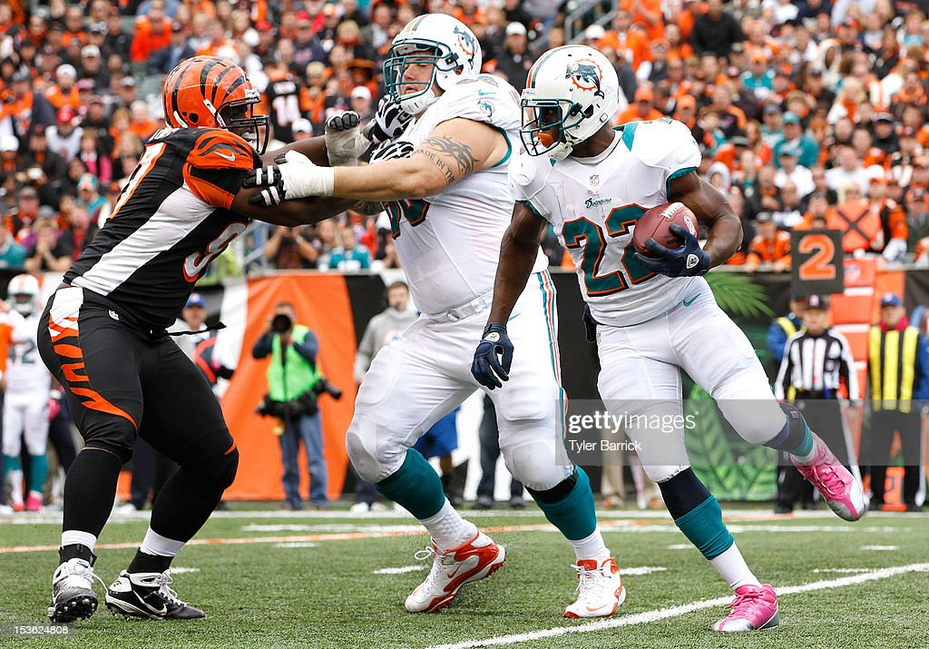 Running back Reggie Bush #22 of the Miami Dolphins, looks for an opening in the line as Richie Incognito, #68 of the Miami Dolphins, blocks Geno Atkins, #97 of the Cincinnati Bengals at Paul Brown Stadium on October 7, 2012 in Cincinnati, Ohio.