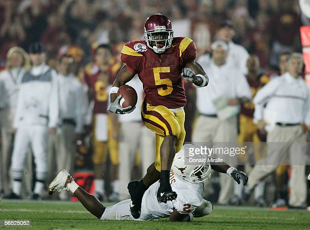 Running back Reggie Bush of the USC Trojans carries the football past Aaron Harris of the Texas Longhorns before fumbling the ball on the play in the...