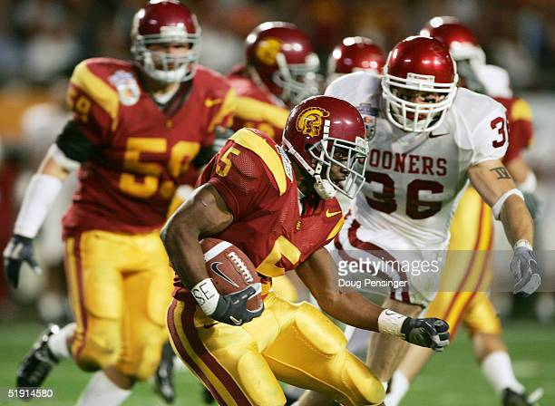 Running back Reggie Bush of the USC Trojans carries the football against the Oklahoma Sooners defense in the second quarter during the FedEx Orange...