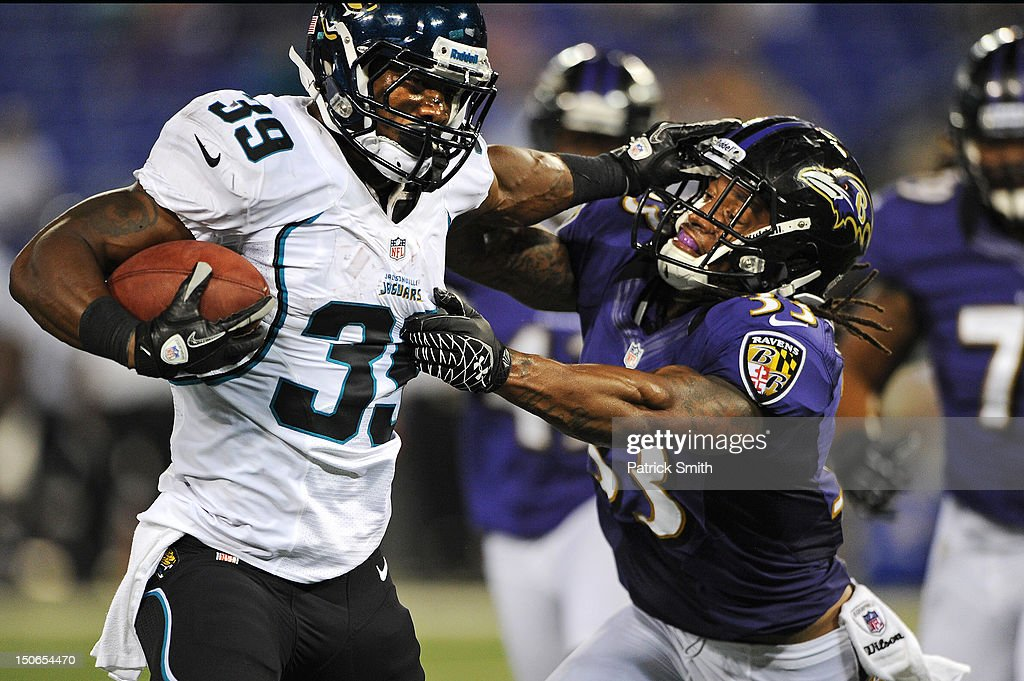 Running back Richard Murphy #39 of the Jacksonville Jaguars stiff arms free safety Christian Thompson #33 of the Baltimore Ravens before scoring a touchdown in the fourth quarter at M&T Bank Stadium on August 23, 2012 in Baltimore, Maryland. The Baltimore Ravens won, 48-17.