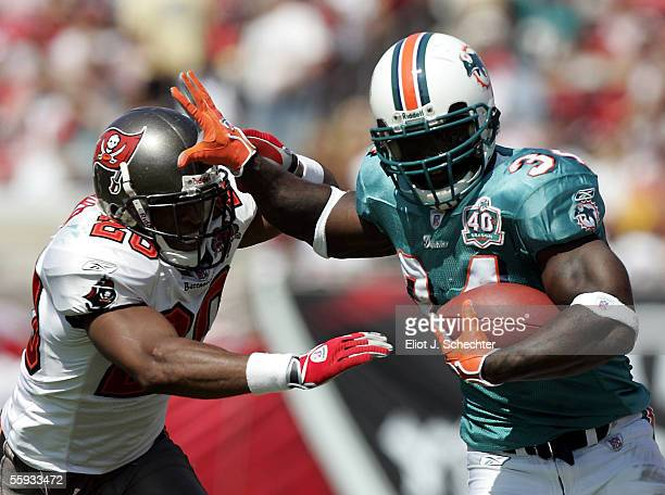 Running back Ricky Williams of the Miami Dolphins is chased out of bounds by cornerback Ronde Barber of the Tampa Bay Buccaneers on October 16 2005...
