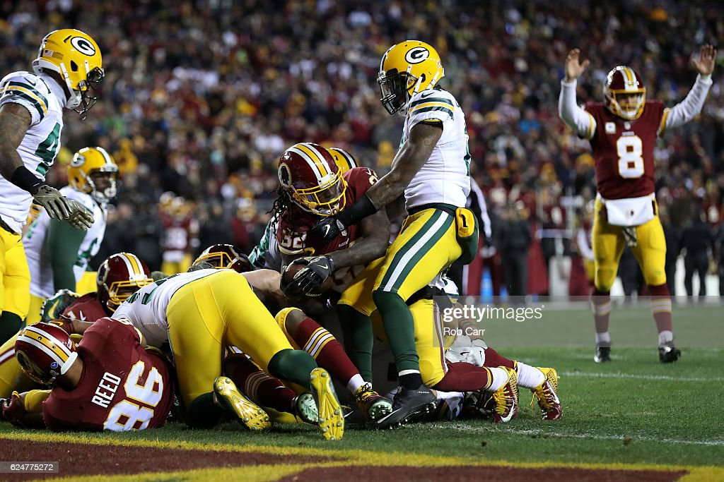 Running back Rob Kelley #32 of the Washington Redskins scores a fourth quarter touchdown while teammate quarterback Kirk Cousins #8 celebrates against the Green Bay Packers at FedExField on November 20, 2016 in Landover, Maryland.