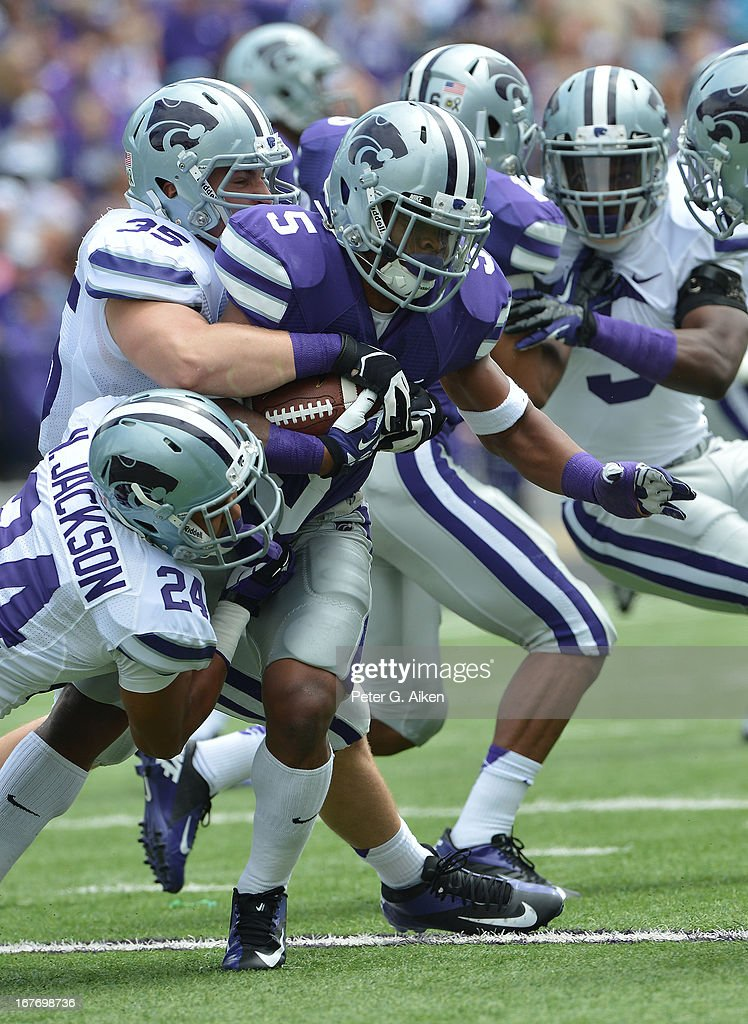 Running back Robert Rose #5 of the Kansas State Wildcats gets tackled by defenders Nate Jackson #24 and Will Davis #35 during the Purple and White Spring Game on April 27, 2013 at Bill Snyder Family Stadium in Manhattan, Kansas.