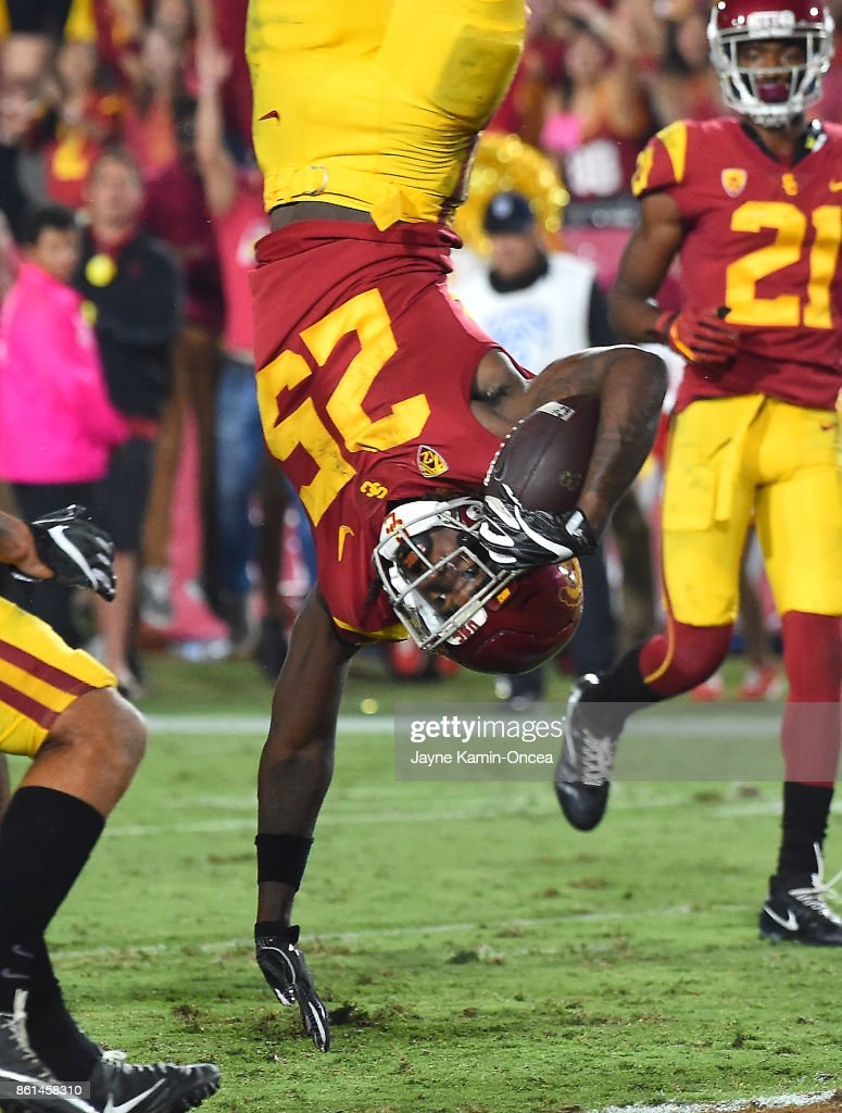 Running back Ronald Jones II #25 of the USC Trojans is upended by defensive back Marquise Blair #13 of the Utah Utes as he flips into the end zone for the go ahead touchdown in the fourth quarter of the game at the Los Angeles Memorial Coliseum on October 14, 2017 in Los Angeles, California.