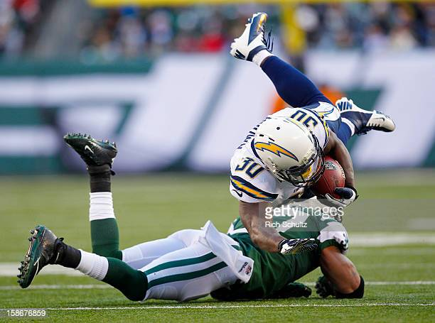 Running back Ronnie Brown of the San Diego Chargers us upended by Yeremiah Bell of the New York Jets during the first half in a game at MetLife...