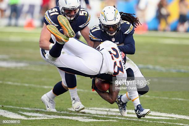 Running back Ronnie Hillman of the Denver Broncos goes airborn as he carries the ball against safety Jahleel Addae and linebacker Kyle Emanuel of the...
