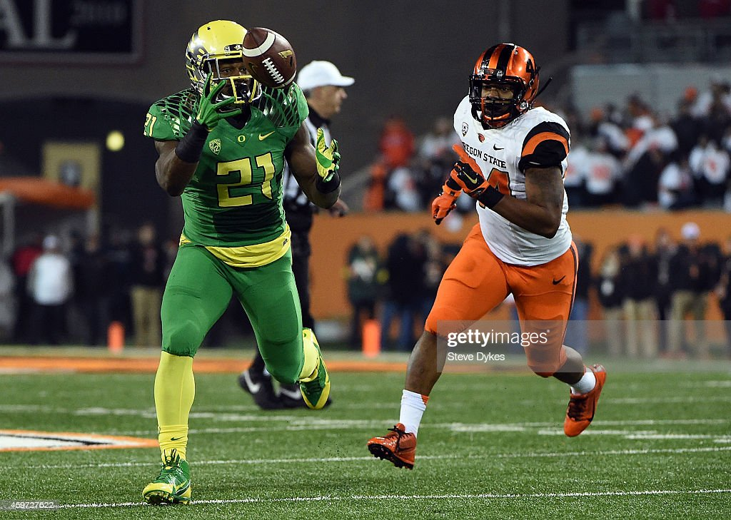 Running back Royce Freeman of the Oregon Ducks juggles the ball as he he catches it and runs it in for a touchdown as linebacker Jabral Johnson of...