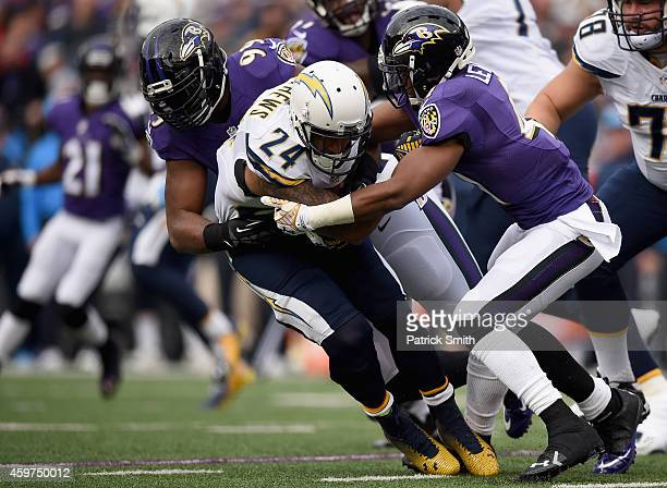 Running back Ryan Mathews of the San Diego Chargers is tackled by defensive end Chris Canty of the Baltimore Ravens and cornerback Anthony Levine...