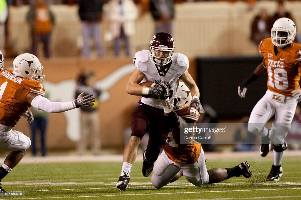 Running back Ryan Swope of Texas A&M #25 tries to break a tackle by University of Texas defensive end Sam Acho #81 during the first half at Darrell K. Royal-Texas Memorial Stadium on November 25, 2010 in Austin, Texas.