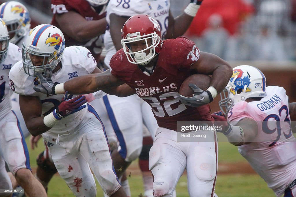 Running back Samaje Perine #32 of the Oklahoma Sooners breaks through the Kansas Jayhawks front line November 22, 2014 at Gaylord Family-Oklahoma Memorial Stadium in Norman, Oklahoma.