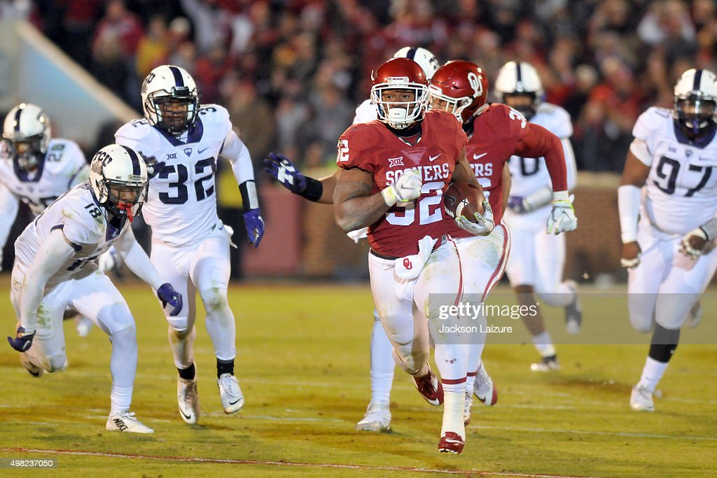 Running back Samaje Perine #32 of the Oklahoma Sooners runs for a second half touchdown past cornerback Nick Orr #18 and linebacker Travin Howard #32 of the TCU Horned Frogs on November 21, 2015 at the Gaylord Family Oklahoma Memorial Stadium in Norman, Oklahoma.