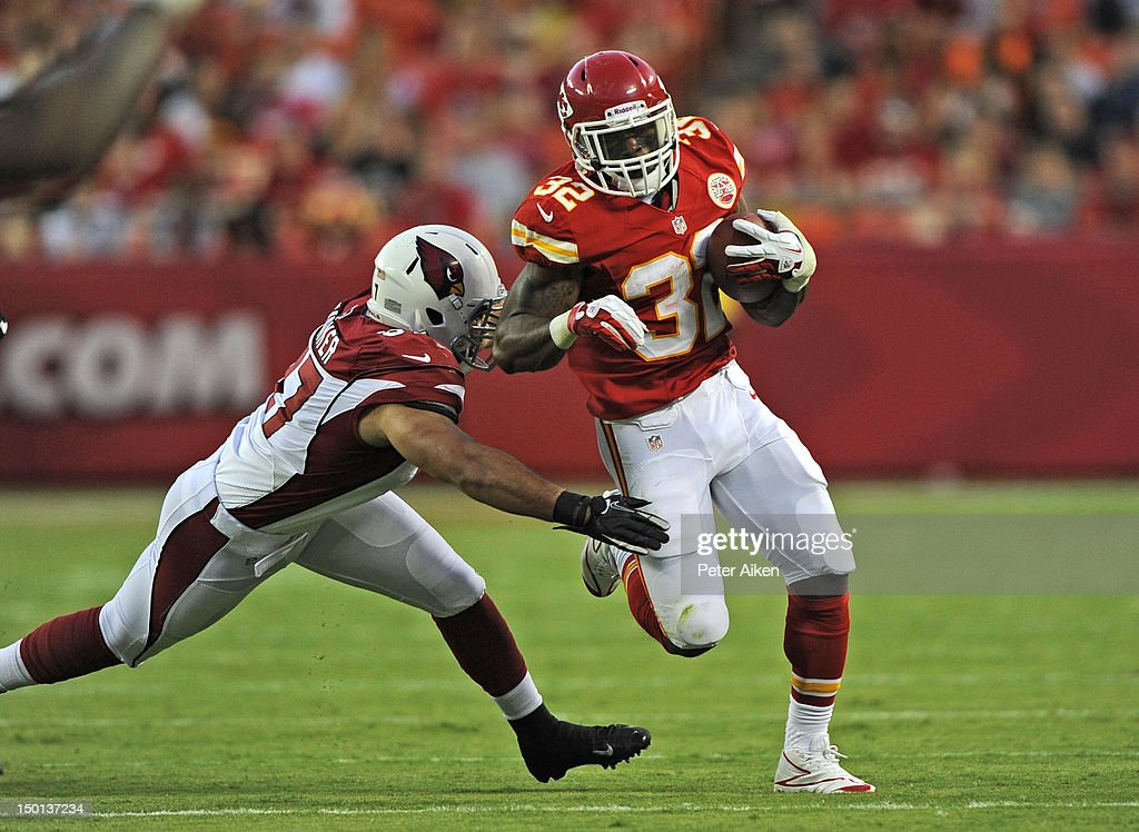 Running back Shaun Draughn #32 of the Kansas City Chiefs rushes against pressure from linebacker Colin Parker #97 of the Arizona Cardinals during the second half on August 10, 2012 at Arrowhead Stadium in Kansas City, Missouri. Kansas City defeated Arizona 27-17.