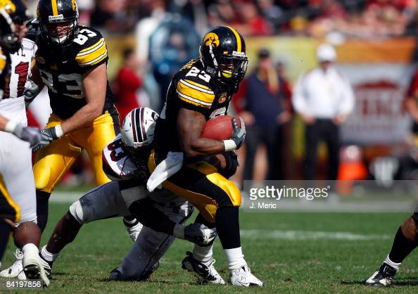 Running back Shonn Greene of the Iowa Hawkeyes attempts to break the tackle of defensive end Cliff Matthews of the South Carolina Gamecocks during...