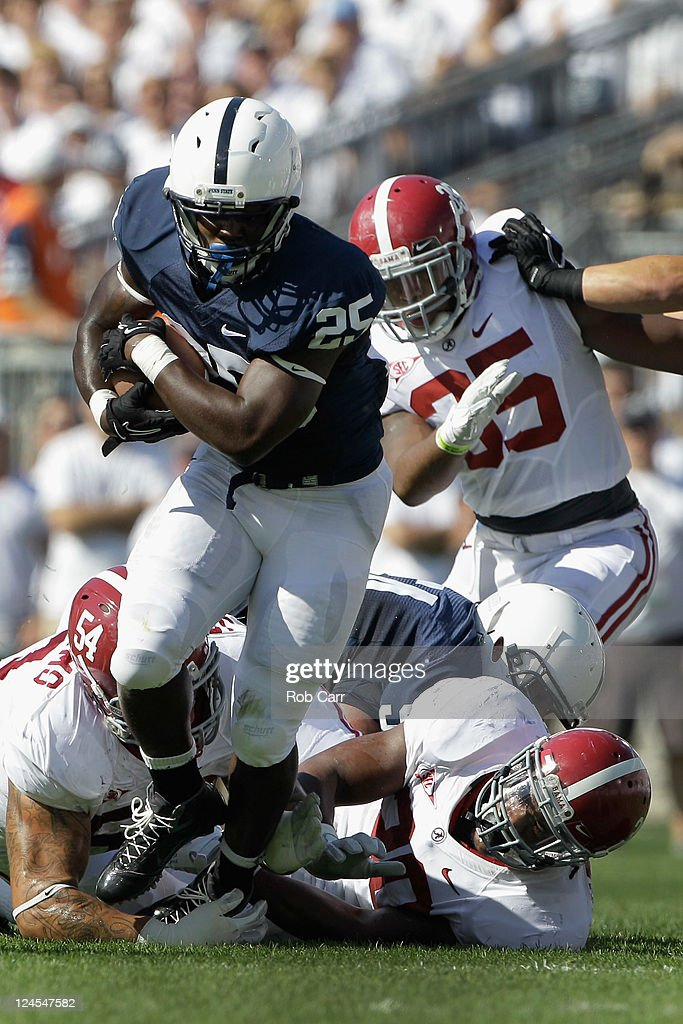 Running back Silas Redd #25 of the Penn State Nittany Lions breaks the tackle of <a gi-track='captionPersonalityLinkClicked' href=/galleries/search?phrase=Jesse+Williams+-+American+Football+Player&family=editorial&specificpeople=11360523 ng-click='$event.stopPropagation()'>Jesse Williams</a> #54 and Dont'a Hightower #30 (R) of the Alabama Crimson Tide during the second half at Beaver Stadium on September 10, 2011 in State College, Pennsylvania.