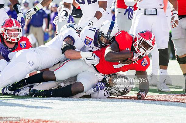 Running back Sony Michel of the Georgia Bulldogs falls into the endzone for a touchdown over linebacker Sammy Douglas of the TCU Horned Frogs at...