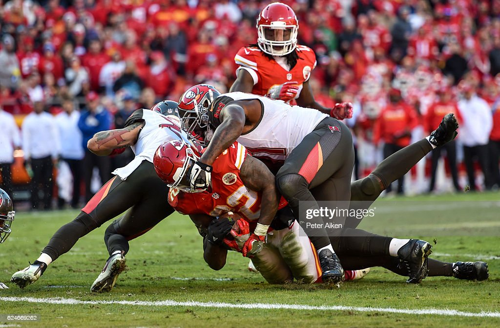 Running back Spencer Ware #32 of the Kansas City Chiefs is tackled by the face mask by defensive end Robert Ayers #91 of the Tampa Bay Buccaneersat Arrowhead Stadium during the fourth quarter of the game on November 20, 2016 in Kansas City, Missouri.