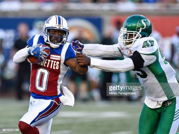 Running back Stefan Logan of the Montreal Alouettes protects the ball from defensive lineman AC Leonard of the Saskatchewan Roughriders in the first...