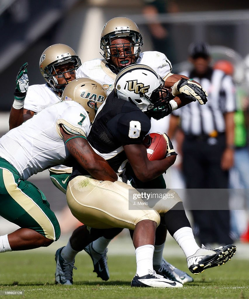 Running back Storm Johnson #8 of the Central Florida Knights is tackled by defenders Greg Irvin #7 and Calvin Jones #11 of the Alabama Birmingham Blazers during the game at Bright House Networks Stadium on November 24, 2012 in Orlando, Florida.
