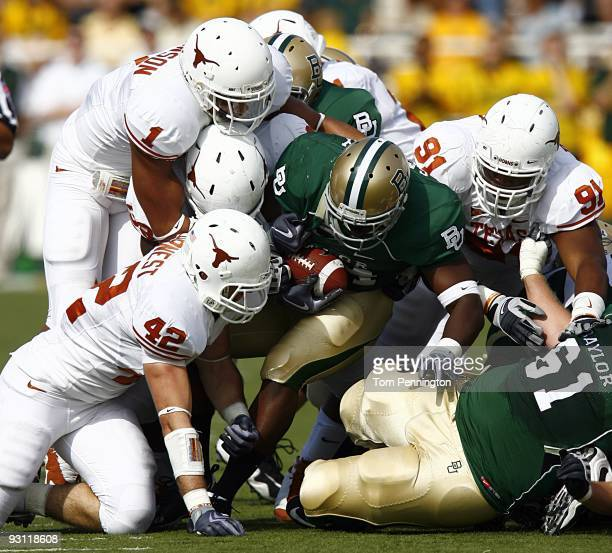 Running back Terrance Ganaway of the Baylor Bears carries the ball against linebacker Dusting Earnest linebacker Keenan Robinson and tackle Kheeston...