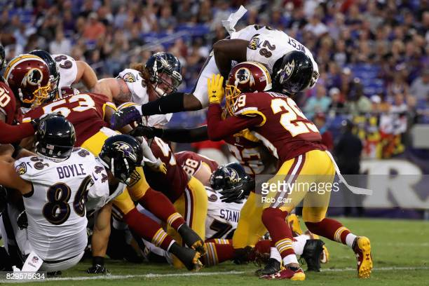 Running back Terrance West of the Baltimore Ravens is hit by cornerback Kendall Fuller of the Washington Redskins while scoring a first quarter...