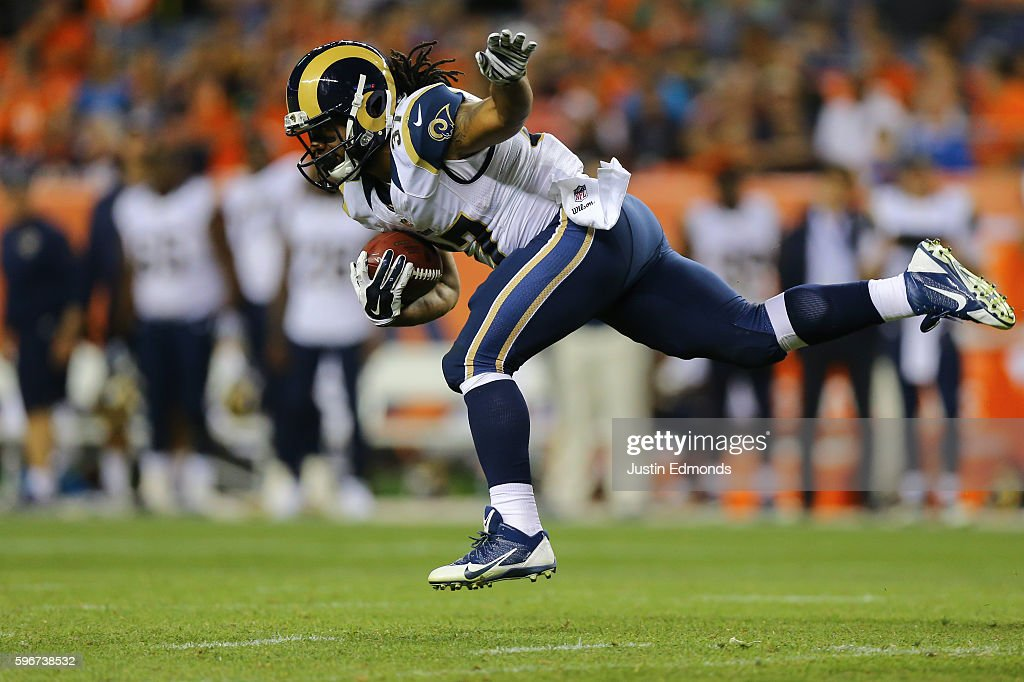 Running back Terrence Magee #37 of the Los Angeles Rams keeps his balance after getting hit on his way to a large gain and a first down during the fourth quarter against the Denver Broncos at Sports Authority Field at Mile High on August 27, 2016 in Denver, Colorado. The Broncos defeated the Rams 17-9 in pre-season action.