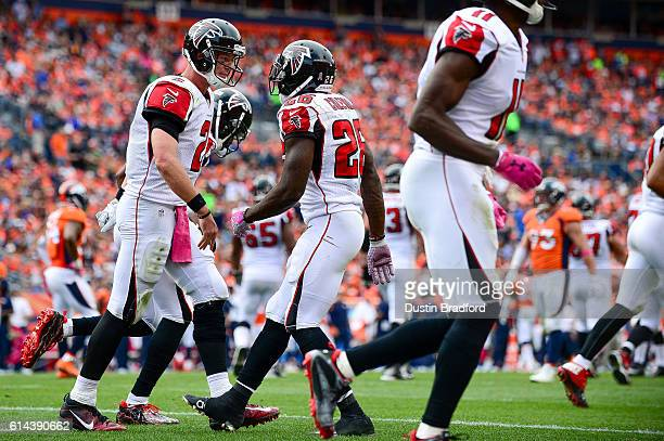 Running back Tevin Coleman of the Atlanta Falcons celebrates with Matt Ryan after scoring a touchdown in the third quarter of the game against the...
