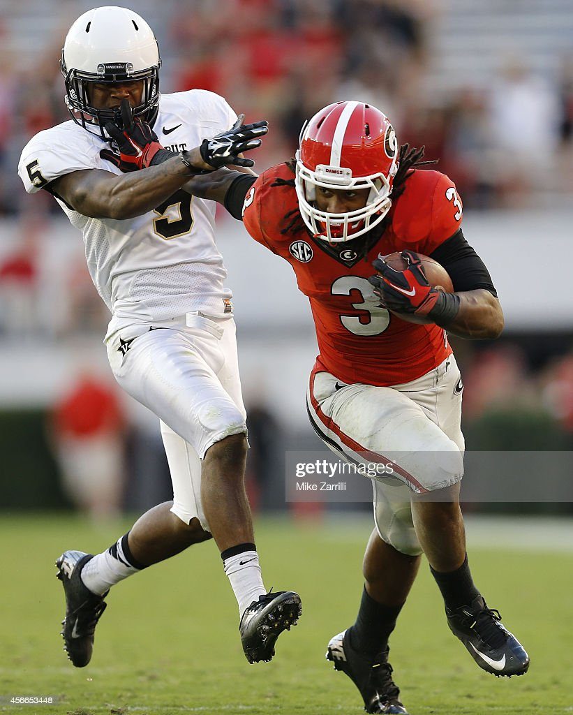 Running back <a gi-track='captionPersonalityLinkClicked' href=/galleries/search?phrase=Todd+Gurley&family=editorial&specificpeople=9688396 ng-click='$event.stopPropagation()'>Todd Gurley</a> #3 of the Georgia Bulldogs stiff arms cornerback Torren McGaster #5 of the Vanderbilt Commodores during a running play in the game at Sanford Stadium on October 4, 2014 in Athens, Georgia.