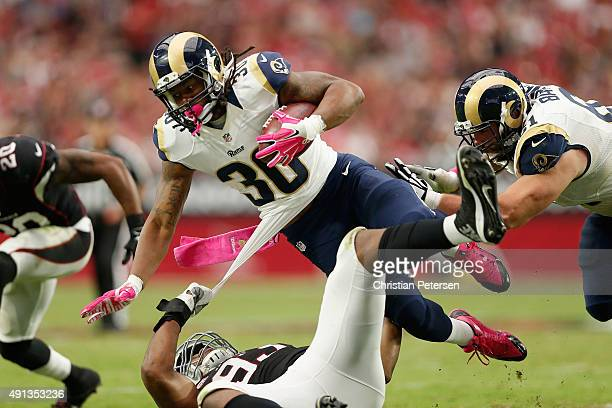 Running back Todd Gurley of the St Louis Rams is tripped up by defensive end Calais Campbell of the Arizona Cardinals during the second half of the...