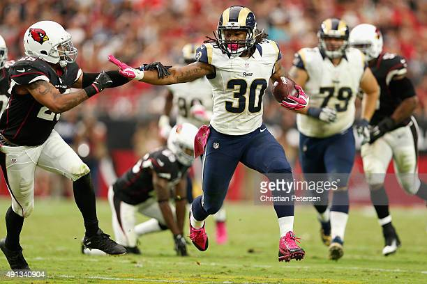Running back Todd Gurley of the St Louis Rams runs past free safety Rashad Johnson of the Arizona Cardinals during the second half of the NFL game at...