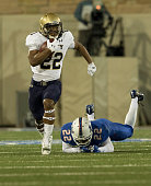 Running back Toneo Gulley of the Navy Midshipmen escapes a tackle by safety Jeremy Brady of the Tulsa Golden Hurricane and runs for a touch down...