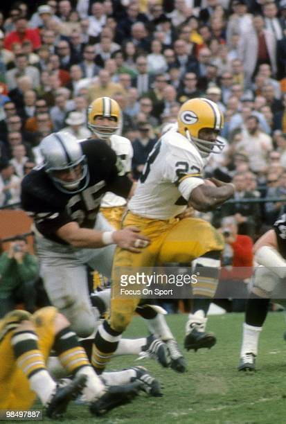 Running Back Travis Williams of the Green Bay Packers carries the ball running out of the grasp of linebacker Dan Conners of the Oakland Raiders...