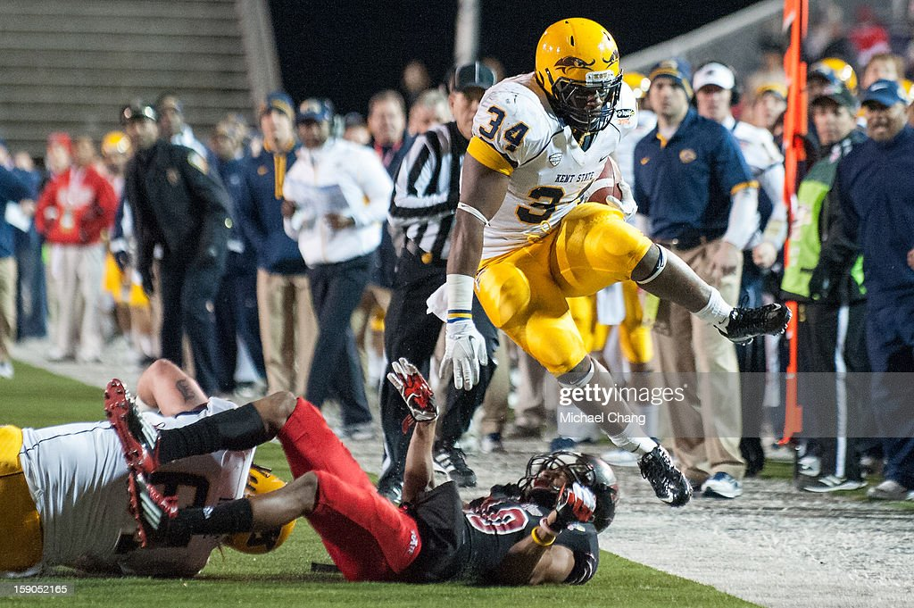 Running back Trayion Durham #34 of the Kent State Golden Flashes leaps over Defensive back Artez Brown #10 of the Arkansas State Red Wolves on January 6, 2013 at Ladd-Peebles Stadium in Mobile, Alabama. Arkansas State defeated Kent State 17-13.