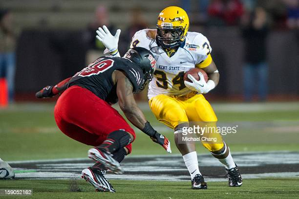 Running back Trayion Durham of the Kent State Golden Flashes prepares to maneuver around Linebacker Qushaun Lee of the Arkansas State Red Wolves on...