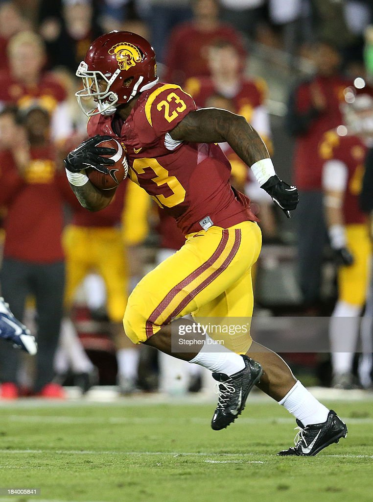Running back Tre Madden #23 of the USC Trojans carries the ball after the catch as he scores on a 63 yard touchdown pass play in the first quarter against the Arizona Wildcats at Los Angeles Coliseum on October 10, 2013 in Los Angeles, California.