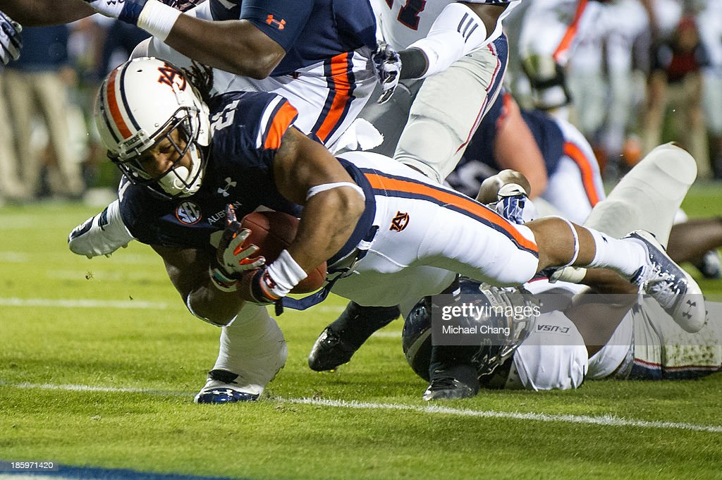 Running back Tre Mason #21 of the Auburn Tigers dives into the end zone as he is being tackled by linebacker Adarius Glanton #4 of the Florida Atlantic Owls during the first quarter of play on October 26, 2013 at Jordan-Hare Stadium in Auburn, Alabama. At the end of the first quarter Auburn leads Florida Atlantic 21-0.