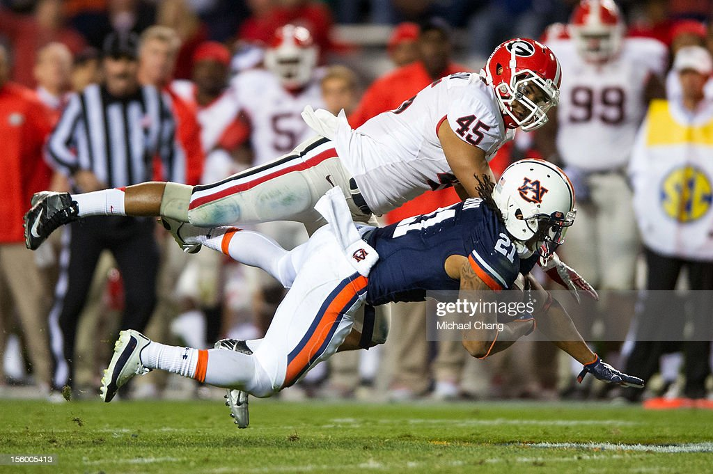 Running back Tre Mason #21 of the Auburn Tigers goes airborne after being hit by linebacker Christian Robinson #45 of the Georgia Bulldogs on November 10, 2012 at Jordan-Hare Stadium in Auburn, Alabama. Georgia defeated Auburn 38-0 and clinched the SEC East division.
