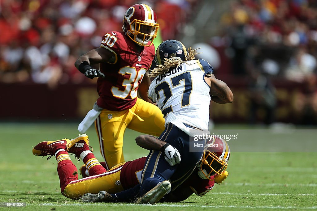 Running back Tre Mason of the St Louis Rams is tackled by cornerback DeAngelo Hall of the Washington Redskins while strong safety Kyshoen Jarrett of...