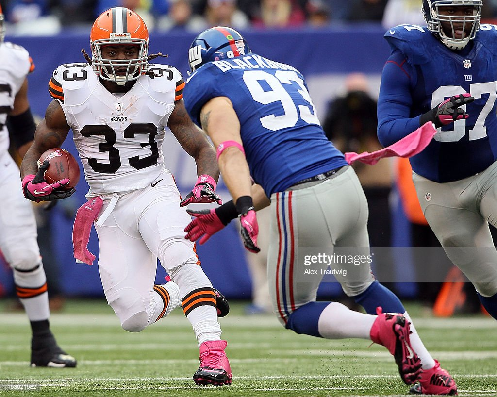 Running back Trent Richardson of the Cleveland Browns avoids a tackle by middle linebacker Chase Blackburn of the New York Giants during their game...
