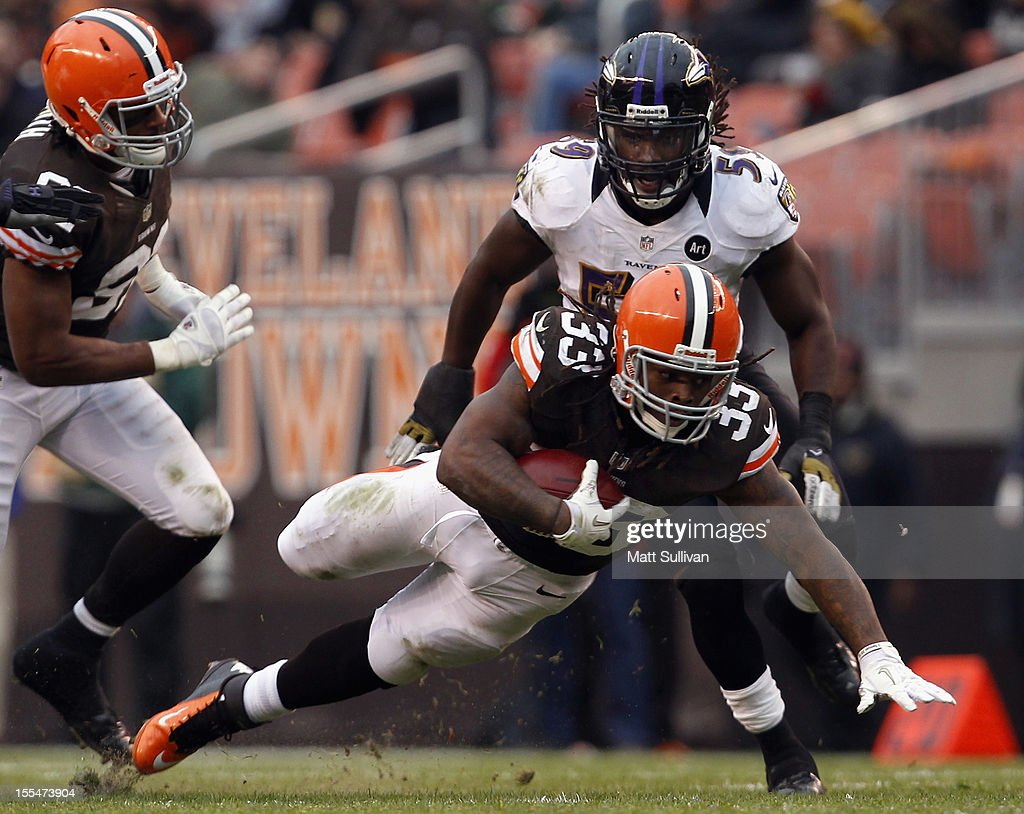 Running back <a gi-track='captionPersonalityLinkClicked' href=/galleries/search?phrase=Trent+Richardson&family=editorial&specificpeople=5653463 ng-click='$event.stopPropagation()'>Trent Richardson</a> #33 of the Cleveland Browns dives for extra yardage in front of linebacker Dannell Ellerbe #59 of the Baltimore Ravens at Cleveland Browns Stadium on November 4, 2012 in Cleveland, Ohio.