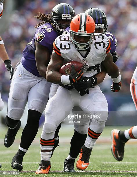 Running back Trent Richardson of the Cleveland Browns is tackled by inside linebacker Daryl Smith and inside linebacker Josh Bynes of the Baltimore...