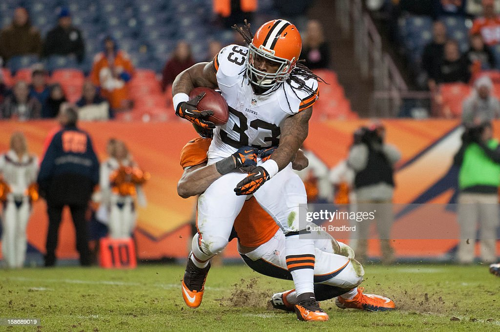 Running back Trent Richardson #33 of the Cleveland Browns is wrapped up as he rushes against the Denver Broncos during a game at at Sports Authority Field Field at Mile High on December 23, 2012 in Denver, Colorado. The Broncos defeated the Browns 34-12.
