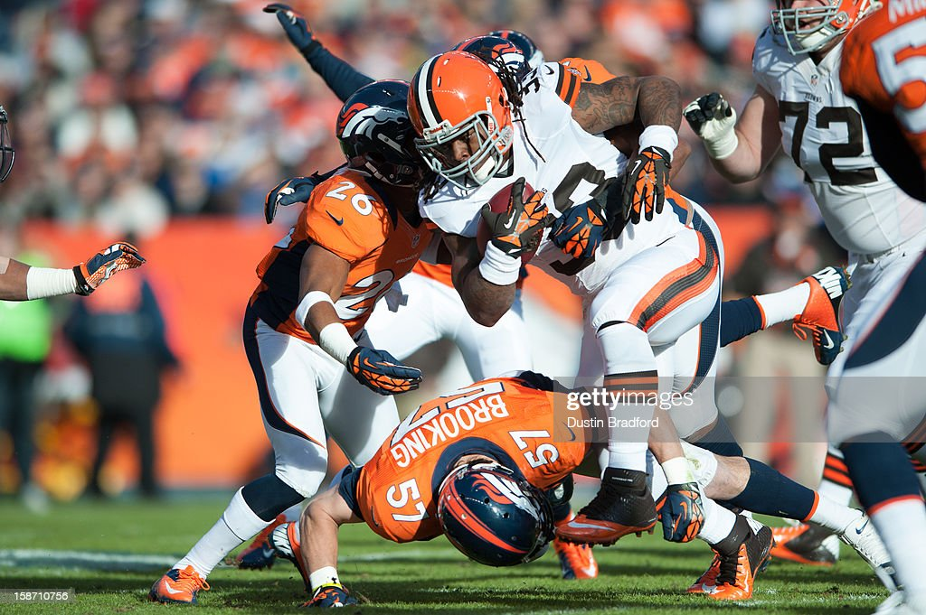 Running back Trent Richardson #33 of the Cleveland Browns rushes against free safety Rahim Moore #26 and middle linebacker Keith Brooking #57 of the Denver Broncos during a game at Sports Authority Field at Mile High on December 23, 2012 in Denver, Colorado. The Broncos defeated the Browns 34-12.