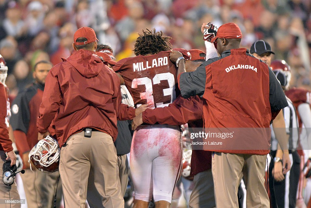Running back Trey Millard #33 of the Oklahoma Sooners is helped off the field by training staff after a knee injury during the fourth quarter of their win against the Texas Tech Red Raiders on October 26, 2013 at Gaylord Family Oklahoma Memorial Stadium in Norman, Oklahoma.