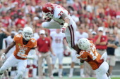 Running back Trey Millard of the Oklahoma Sooners tries to hurdle safety Adrian Phillips in front of safety Mykkele Thompson of the Texas Longhorns...