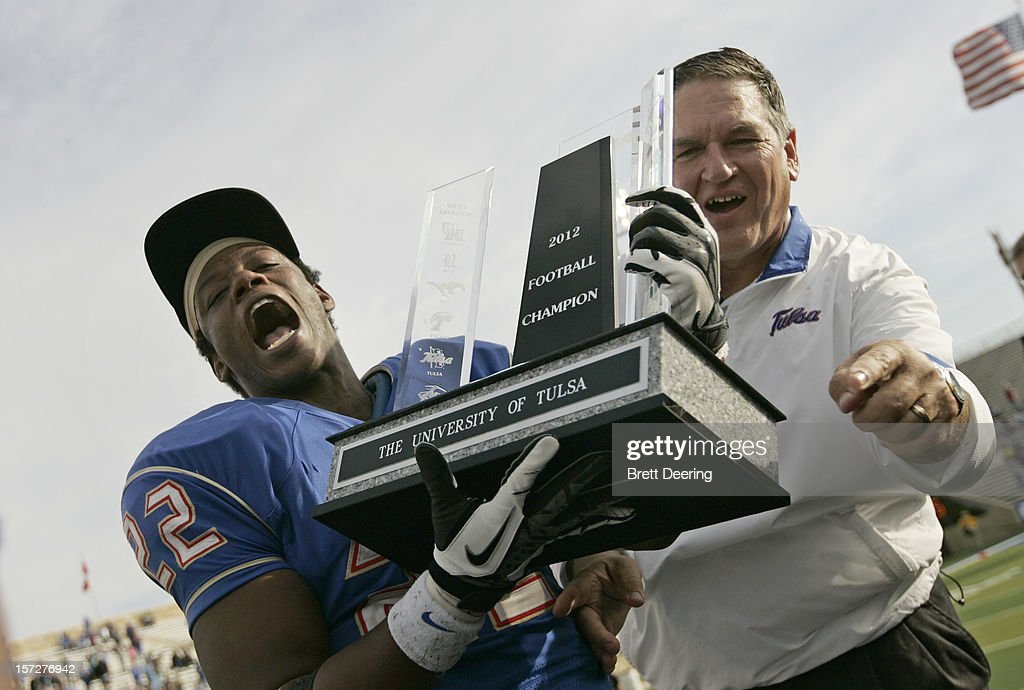Running back Trey Watts #22 and Head Coach Bill Blankenship of the Tulsa Golden Hurricane hold the championship trophy after the C-USA championship game against the Central Florida Knights on December 1, 2012 at H.A. Chapman Stadium in Tulsa, Oklahoma. Tulsa defeated Central Florida 33-27 in overtime.
