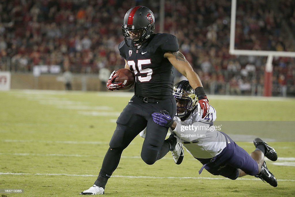 Running back Tyler Gaffney #25 of the Stanford Cardinal rushes for a touchdown as linebacker Travis Feeney #41 of the Washington Huskies tackles during the fourth quarter of their game on October 5, 2013 at Stanford Stadium in Stanford, California.