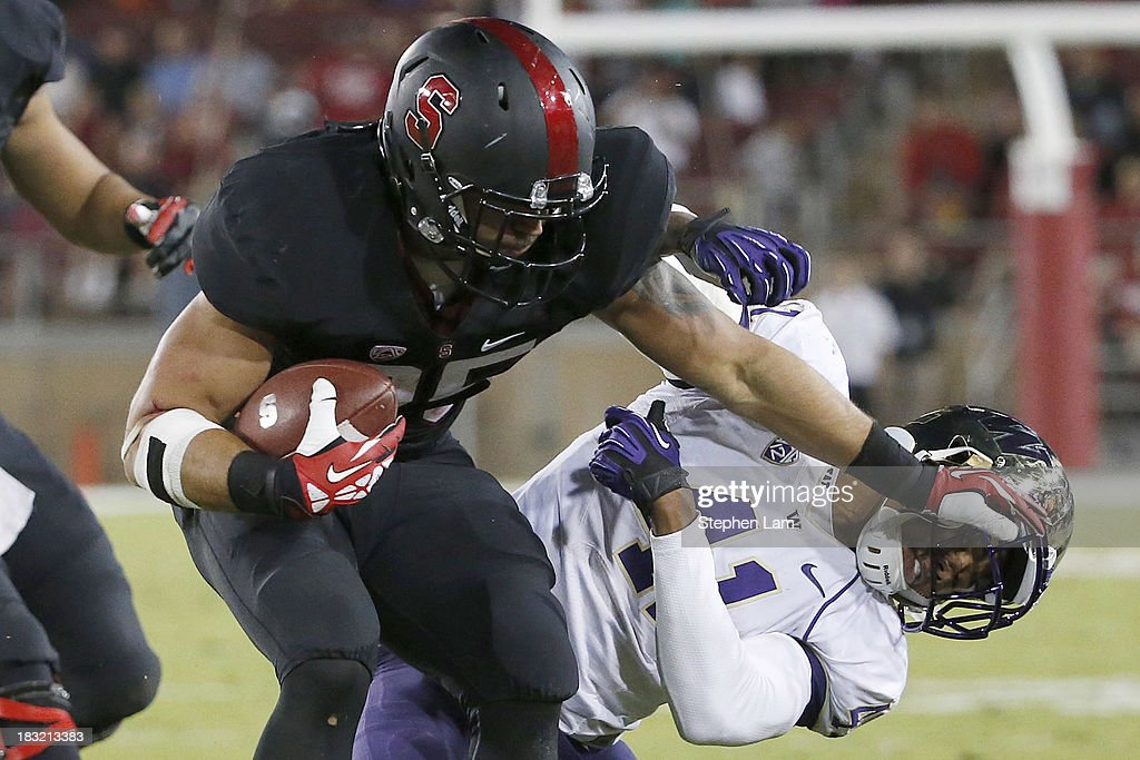 Running back Tyler Gaffney #25 of the Stanford Cardinal stiff-arms linebacker Travis Feeney #41 of the Washington Huskies tackles during the fourth quarter of their game on October 5, 2013 at Stanford Stadium in Stanford, California.