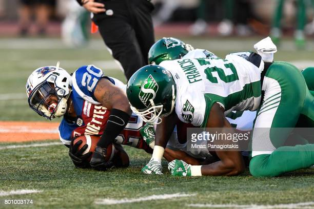 Running back Tyrell Sutton of the Montreal Alouettes is tackled in the first half against the Saskatchewan Roughriders during the CFL game at...